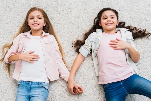 Een bovenaanzicht van ontspannen twee meisjes liggend op tapijt opzoeken