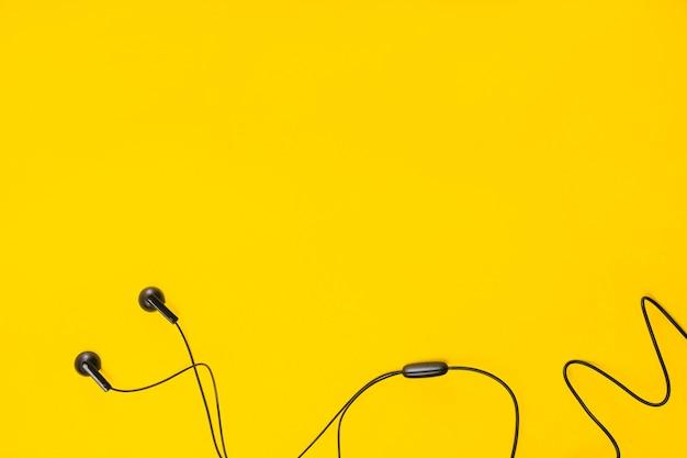 Een bovenaanzicht van oortelefoon op gele achtergrond met ruimte voor tekst