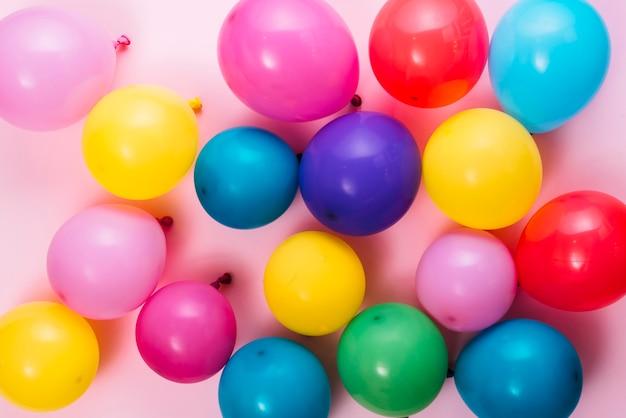 Een bovenaanzicht van opgeblazen kleurrijke ballonnen over roze achtergrond