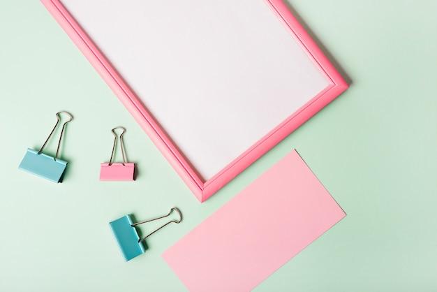Een bovenaanzicht van paperclips; leeg roze papier en wit frame op pastel gekleurde achtergrond