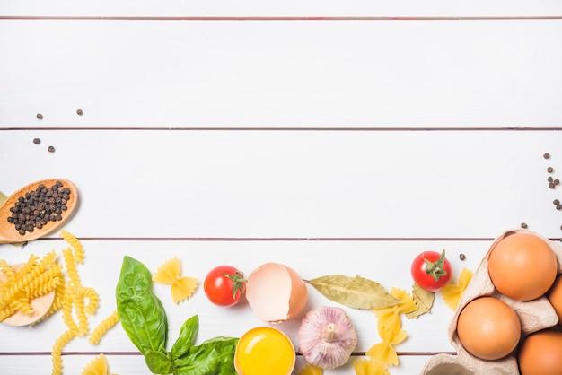 Een bovenaanzicht van pasta-ingrediënten op witte houten plank