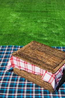Een bovenaanzicht van picknickmand op geruite tafel over groene grasmat