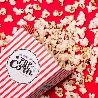 Een bovenaanzicht van popcorn gemorst op rode achtergrond