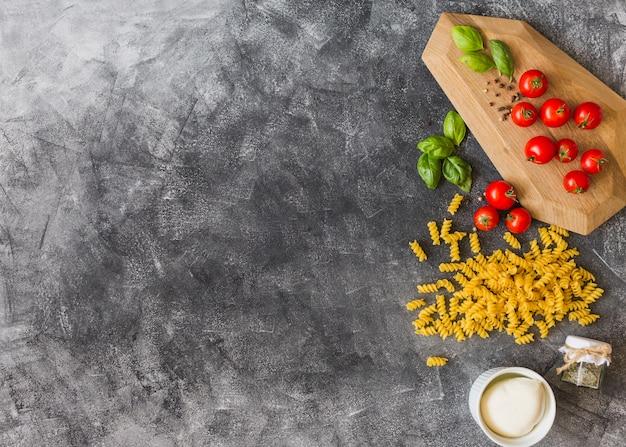 Een bovenaanzicht van rauwe fusilli met ingrediënten over de grunge achtergrond