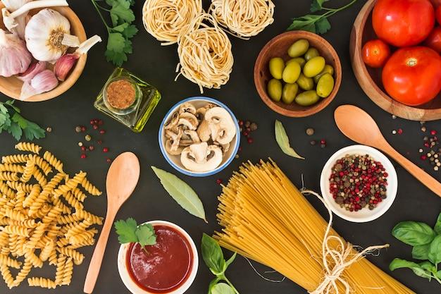 Een bovenaanzicht van rauwe pasta met ingrediënten op zwarte achtergrond