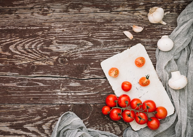 Een bovenaanzicht van rode kersentomaten; knoflookteentjes en champignons op houten tafel