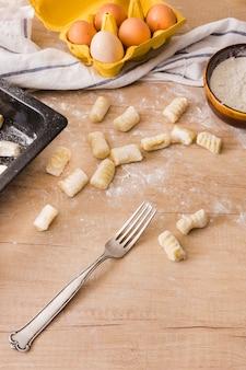 Een bovenaanzicht van roestvrijstalen vork met pasta gnocchi deeg; eieren en meel op houten tafel