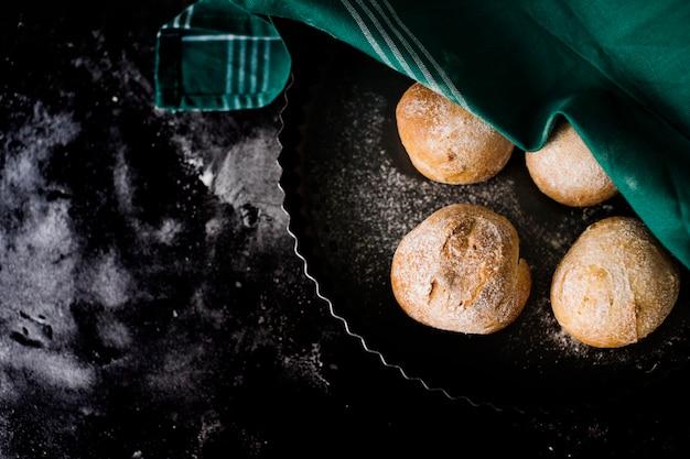 Een bovenaanzicht van rond gebakken brood op de marmeren blad