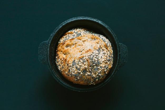 Een bovenaanzicht van rond gebakken brood op de zwarte achtergrond