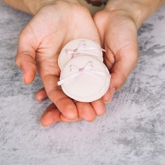 Een bovenaanzicht van roze bitterkoekjes met strik in de handen