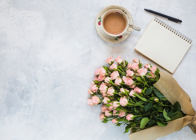 Een bovenaanzicht van roze bloemboeket; koffiekop; spiraal kladblok en pen op concrete achtergrond