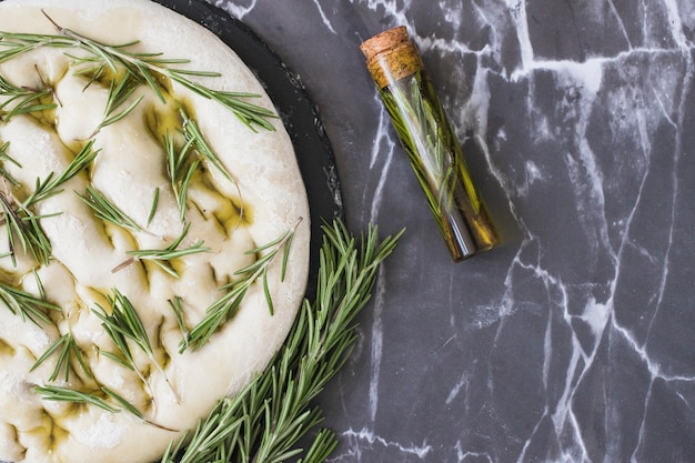 Een bovenaanzicht van rozemarijn kruiden op ongekookt brood deeg over marmeren blad
