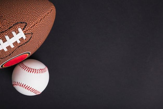 Een bovenaanzicht van rugbybal en honkbal op zwarte achtergrond