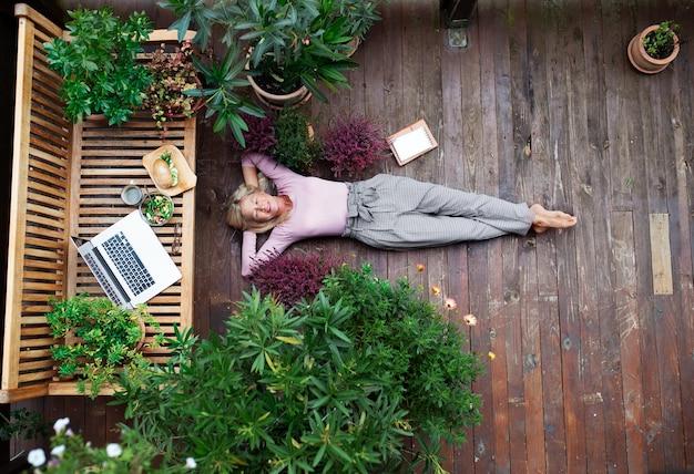 Een bovenaanzicht van senior vrouw met laptop buiten op terras liggen, rusten.