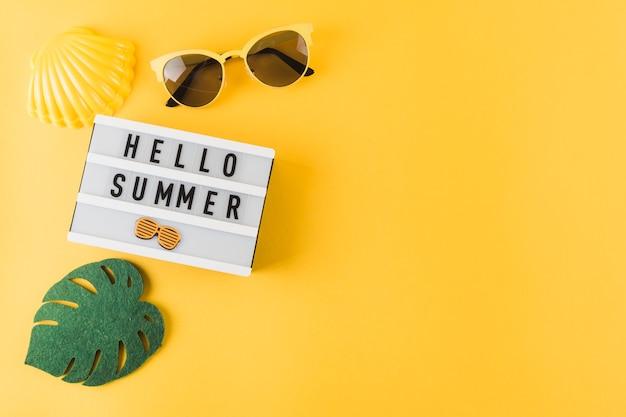 Een bovenaanzicht van sint-jakobsschelp; zonnebril; blad en hallo zomer lichtbak op gele achtergrond