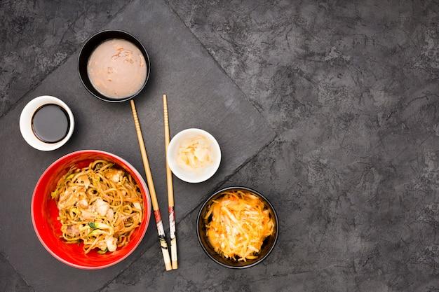 Een bovenaanzicht van smakelijke chinees eten over zwarte ondergrond