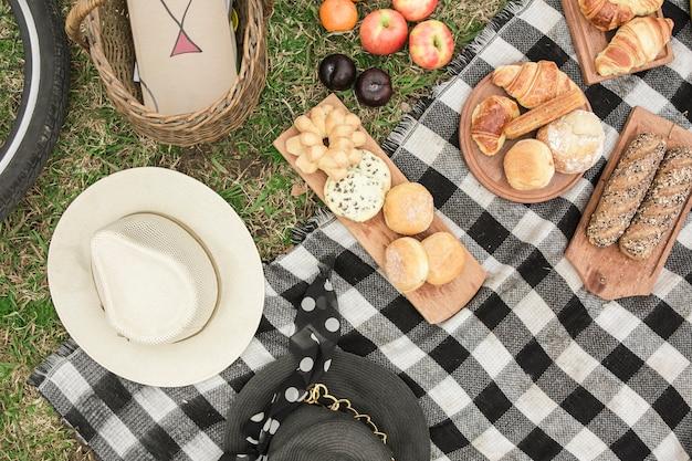 Een bovenaanzicht van snacks en fruit op een picknick in het park