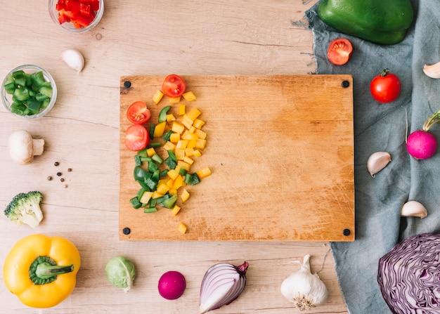 Een bovenaanzicht van snijplank met gehakte groenten op houten tafel