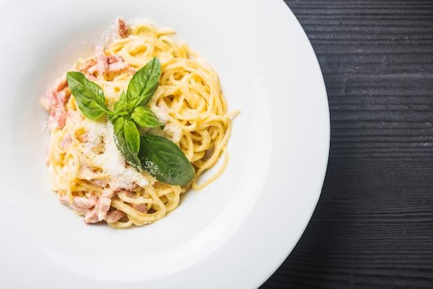 Een bovenaanzicht van spaghetti met basilicumblad en kaas sierlaagjes