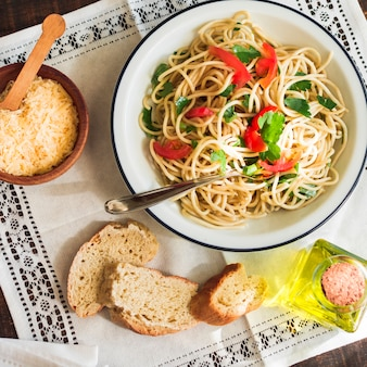 Een bovenaanzicht van spaghetti op plaat met geraspte kaas; brood en olijfolie op placemat