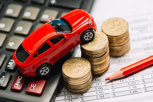 Een bovenaanzicht van speelgoedauto over calculator en muntstukstapel op financieel rapport