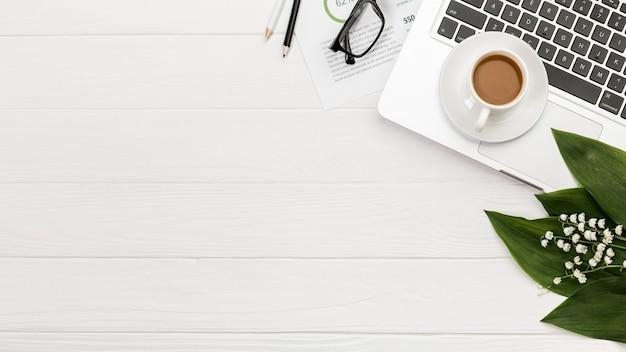 Een bovenaanzicht van spiraal kladblok op laptop met koffiekopje op het bureau