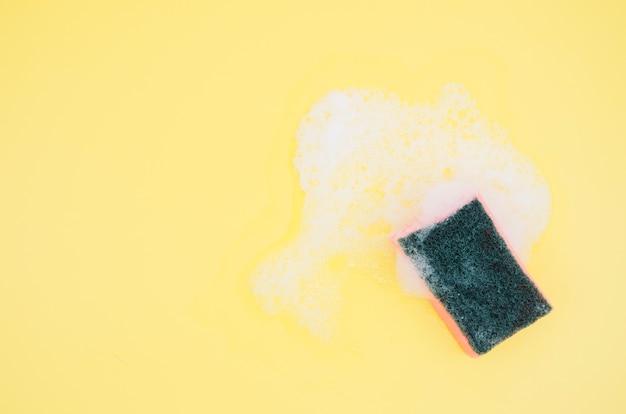 Een bovenaanzicht van spons met zeep sud op gele achtergrond