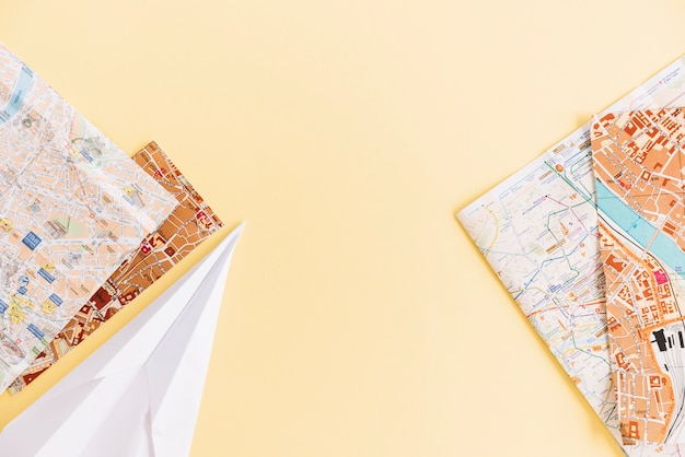 Een bovenaanzicht van steden wegenkaarten en papieren vliegtuigje op gekleurde achtergrond