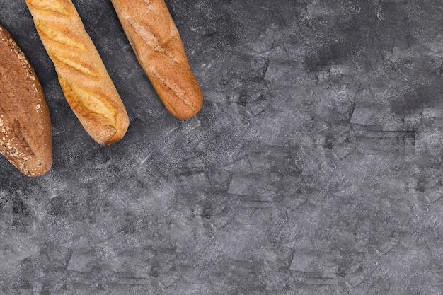 Een bovenaanzicht van stokbrood en brood op de hoek van de zwarte gestructureerde achtergrond