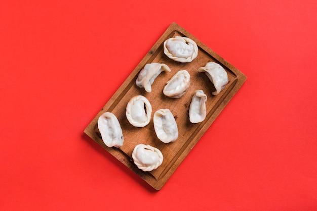 Een bovenaanzicht van stoom dumplings op houten dienblad tegen rode achtergrond
