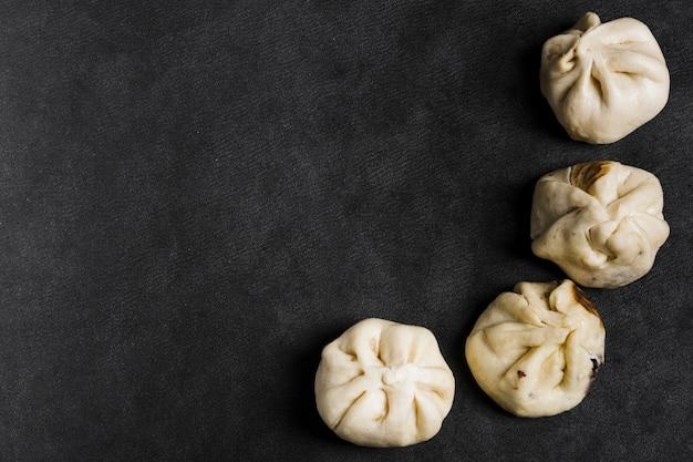 Een bovenaanzicht van stoom dumplings op zwarte textuur achtergrond