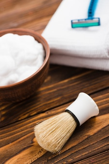 Een bovenaanzicht van synthetische scheerkwast met onscherp schuim; servet en scheermes op houten bureau