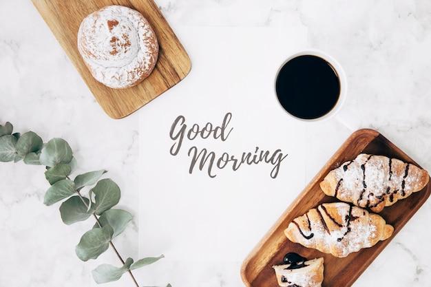Een bovenaanzicht van takje; koffie; broodje en croissants met goedemorgenbericht over marmeren textuurachtergrond