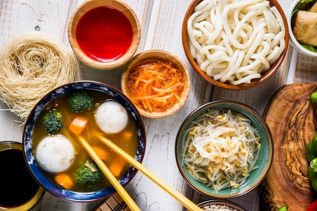 Een bovenaanzicht van thaise vis en plantaardige kom soep met udon noedels; saus en bonenspruiten op wit bureau