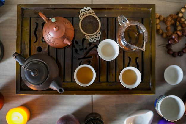 Een bovenaanzicht van theeservies op houten dienblad met brandende kaars