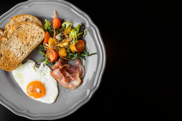 Een bovenaanzicht van toast; spek; salade en gebakken eieren op grijze plaat op zwarte achtergrond