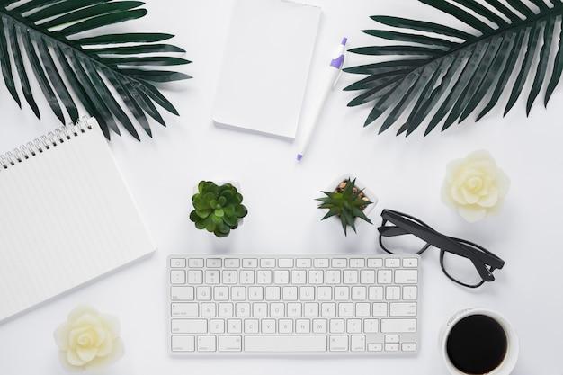 Een bovenaanzicht van toetsenbord met kantoorbenodigdheden en bladeren op een witte achtergrond