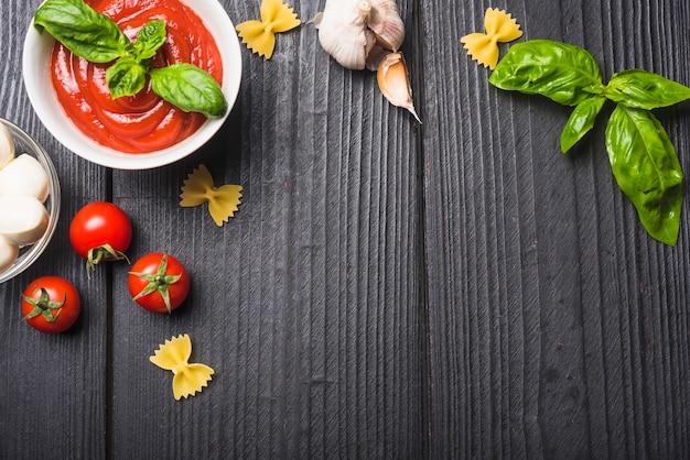 Een bovenaanzicht van tomatensaus met mozzarella; pasta; knoflook een basilicum op houten plank