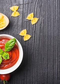 Een bovenaanzicht van tomatensaus met ongekookte pasta op zwarte houten achtergrond