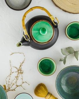 Een bovenaanzicht van traditionele chinese thee set met penseel op witte gestructureerde achtergrond