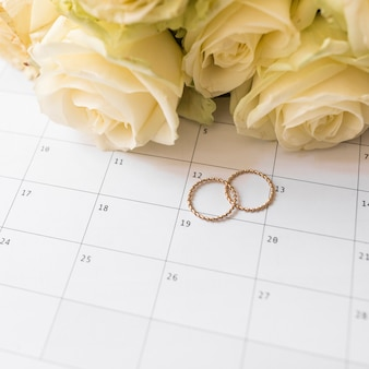 Een bovenaanzicht van trouwringen en rozen op kalender