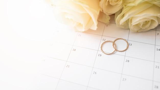 Een bovenaanzicht van trouwringen op kalenderdatum met rozen