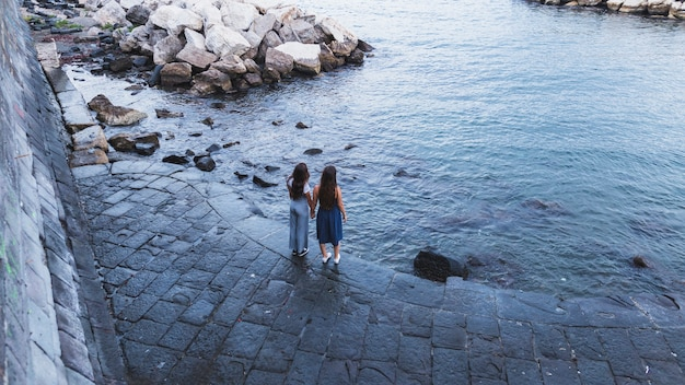 Een bovenaanzicht van twee jonge vrouwen staan in de buurt van de kust