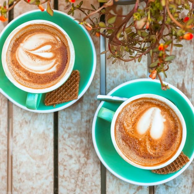 Een bovenaanzicht van twee koffiekopje met hartvorm latte art