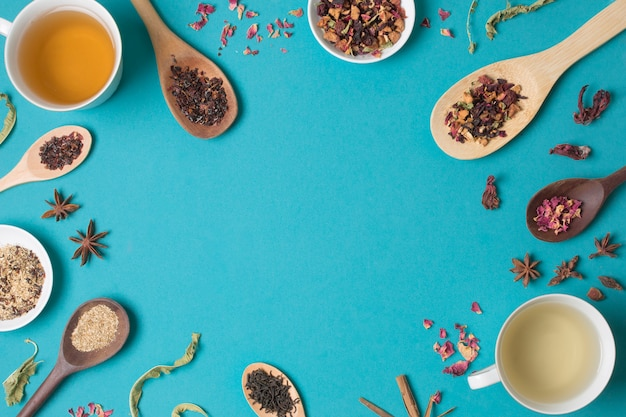 Een bovenaanzicht van verschillende gedroogde kruiden en thee op blauwe achtergrond