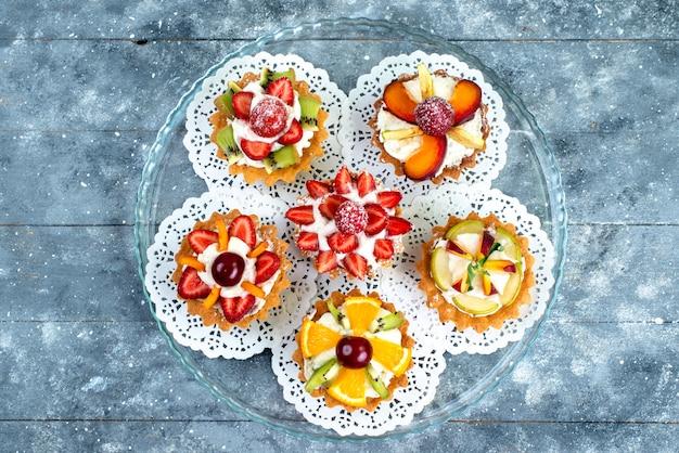 Een bovenaanzicht van verschillende kleine cakes met room en vers gesneden fruit op het grijsblauwe koekje van de fruitcake
