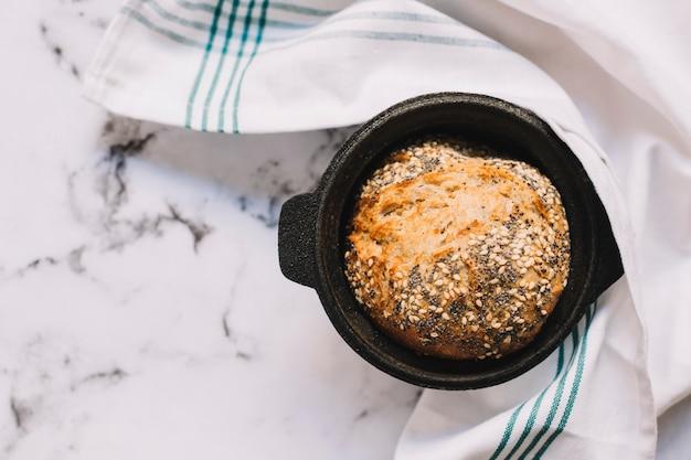 Een bovenaanzicht van volkoren brood in zwarte container op marmeren blad