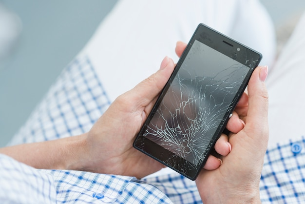 Een bovenaanzicht van vrouw met gebroken mobiele scherm