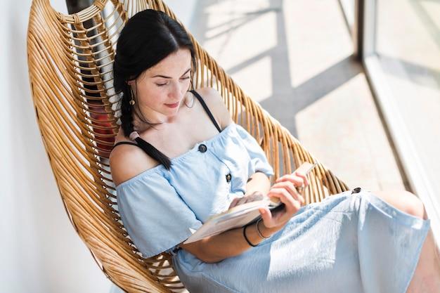 Een bovenaanzicht van vrouw zittend op houten stoel leesboek