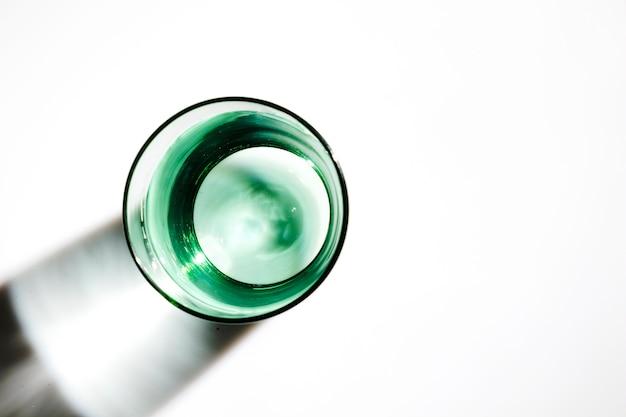 Een bovenaanzicht van water in het groene glas op witte achtergrond